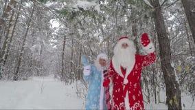 Santa Claus e nipote che ondeggiano le loro mani in un video di movimento lento nevoso dell'abetaia archivi video