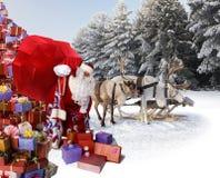 Santa Claus e sua rena com presentes Imagens de Stock