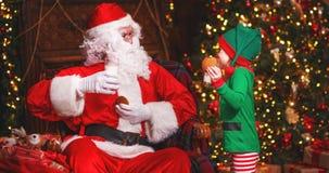 Santa Claus e uma criança do duende em um leite bebendo do Natal que come cookies Fotos de Stock Royalty Free