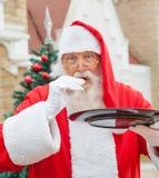 Santa Claus Eating Cookie Against House Arkivbild