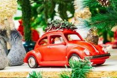 Santa Claus in een rode auto draagt een Kerstboom op het dak van de auto stock afbeelding