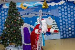 Santa Claus in een rode kaftan dichtbij een geklede boom royalty-vrije stock fotografie