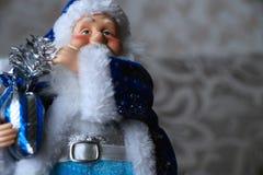 Santa Claus in einem blauen Mantel mit einer Tasche mit Geschenken Stockbild