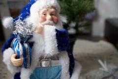 Santa Claus in einem blauen Mantel mit einer Tasche mit Geschenken Stockfoto