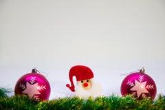 Santa Claus in einem roten Hut in der Mitte und auf den Seiten eines purpurroten Balls auf einem weißen Hintergrund Stockfotografie