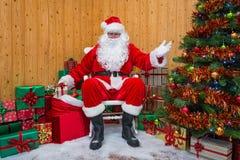 Santa Claus in einer Grotte Geschenke austeilend lizenzfreie stockfotos