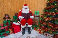 Santa Claus in einer Grotte sein Weihnachtsbuch lesend lizenzfreie stockfotos