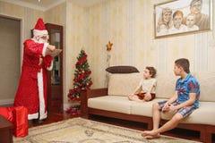 Santa Claus in einer langen hellen Klage und in den Handschuhen erhält Geschenke von der großen roten Tasche - Russland, Moskau,  Lizenzfreies Stockfoto