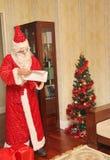Santa Claus in einer langen hellen Klage und in den Handschuhen erhält Geschenke von der großen roten Tasche - Russland, Moskau,  Stockfoto