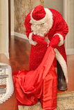 Santa Claus in einer langen hellen Klage und in den Handschuhen erhält Geschenke von der großen roten Tasche - Russland, Moskau,  Stockfotografie