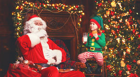 Santa Claus and elf child in Christmas drinking milk and eating Royalty Free Stock Photography