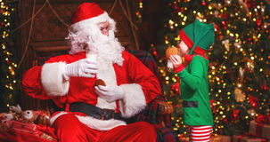 Santa Claus and a elf child in a Christmas drinking milk eating cookies Royalty Free Stock Photos