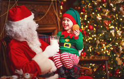 Santa Claus and elf child in Christmas drinking milk and eating Royalty Free Stock Photos