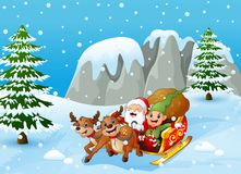 Santa claus and elf sliding in the snowing hill Stock Photography