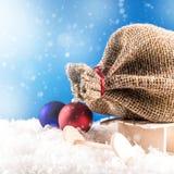 Santa Claus em um pacote de pequenos trenós de madeira Imagem de Stock