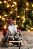 Santa Claus em um pequeno trenó no fundo de luzes de Natal Imagem de Stock