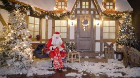 Santa Claus emballe des cadeaux ou les présents dans le sac, se repose en dehors de la maison entre les arbres de Noël, boissons  banque de vidéos