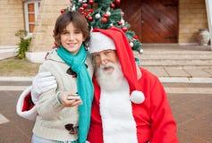 Santa Claus Embracing Boy With Smartphone draußen Stockfotografie