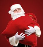 Santa Claus embracing huge red sack with gifts Royalty Free Stock Images