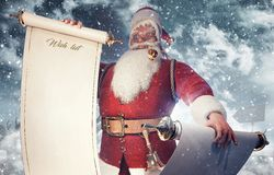 Santa Claus with empty wish list scroll, mock up Christmas background stock illustration