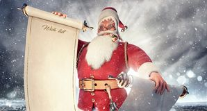 Santa Claus with empty wish list scroll, mock up Christmas background stock image