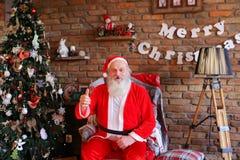 Santa Claus enérgica aumenta el pulgar para arriba, sentándose en la butaca en el FE Fotografía de archivo