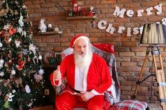 Santa Claus enérgica aumenta el pulgar para arriba, sentándose en la butaca en el FE Imagen de archivo libre de regalías