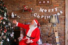 Santa Claus enérgica aumenta el pulgar para arriba, sentándose en la butaca en el FE Imagenes de archivo