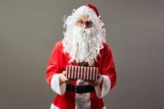 Santa Claus en controles de los vidrios en su mano el regalo de la Navidad del fondo gris imagen de archivo libre de regalías