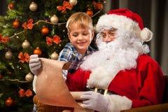 Santa Claus en een kleine jongen Royalty-vrije Stock Afbeeldingen