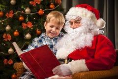Santa Claus en een kleine jongen stock foto's