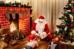 Santa Claus en el piso en la casa da a regalos al niño i fotografía de archivo libre de regalías