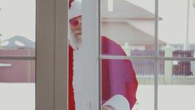 Santa Claus en gafas de sol divertidas viene en casa metrajes