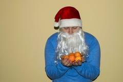 Santa Claus en heel wat Mondarin in zijn handen Stock Afbeelding