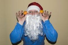 Santa Claus en heel wat twee mandarins in hun handen Stock Fotografie