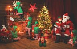 Santa Claus en kleine elf vóór Kerstmis in zijn huis royalty-vrije stock afbeelding