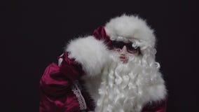 Santa Claus en las gafas de sol que miran buenos niños ausentes y que buscan contra fondo negro metrajes