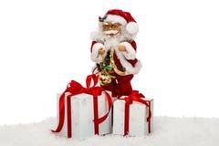 Santa Claus en nieve con las cajas de regalo - juegue, aislado en el CCB blanco Foto de archivo libre de regalías