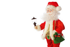 Santa Claus en un traje rojo con un regalo a disposición y una linterna en a Foto de archivo
