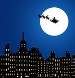 Santa Claus en un trineo debajo de la ciudad de la noche Imagen de archivo