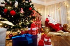 Santa Claus en una silla al lado de la chimenea en la Navidad, nueva Y foto de archivo libre de regalías