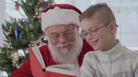 Santa Claus en weinig jongen lezen het boek en het lachen stock video