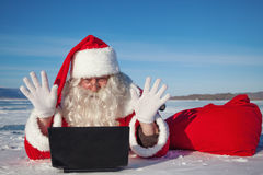 Santa Claus enjoys lying in the snow, looking at l Stock Photo