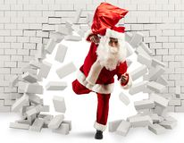 Santa Claus enters to deliver the gift by making a hole in the wall. Christmas is coming. Santa Claus struggling with deliveries royalty free stock photography