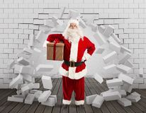 Santa Claus enters to deliver the gift by making a hole in the wall. Christmas is coming. Santa Claus struggling with deliveries royalty free stock images