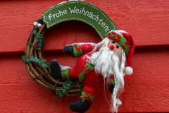 Santa Claus at the entrance to the House. Text in german: Merry Christmas stock photography