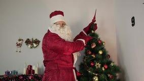 Santa Claus está adornando un árbol de navidad almacen de metraje de vídeo