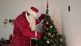 Santa Claus está adornando un árbol de navidad almacen de video