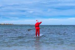 Santa Claus está agitando sobre su tabla hawaiana imágenes de archivo libres de regalías