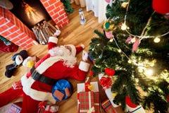 Santa Claus está durmiendo, cansado, bebida en un cuarto cerca del firepla Fotografía de archivo libre de regalías